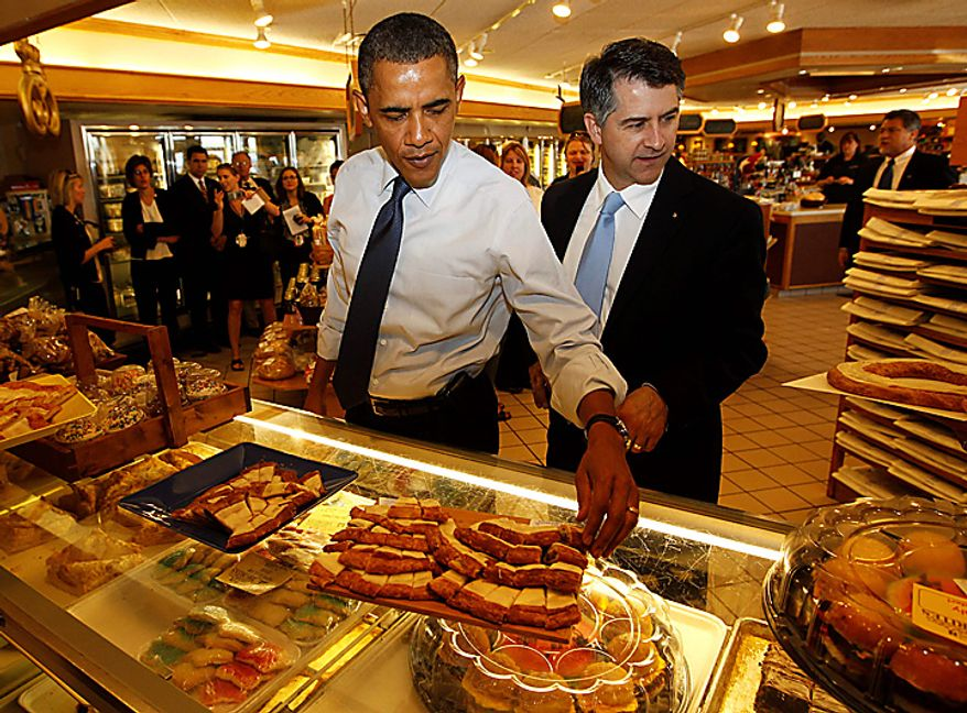 President Barack Obama stands with Racine, Wis. Mayor John Dickert as he tries a pecan kringle during an unscheduled stop at O and H Bakery in Racine, Wis., Wednesday, June 30, 2010. (AP Photo/Charles Dharapak)