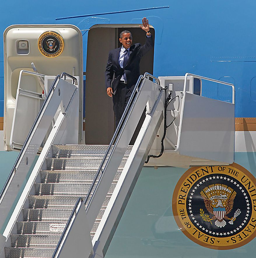 President Barack Obama waves as he exits Air Force One upon his arrival at Mitchell International airport in Milwaukee, Wis., Wednesday, June, 30, 2009.  (AP Photo/Jeffrey Phelps)