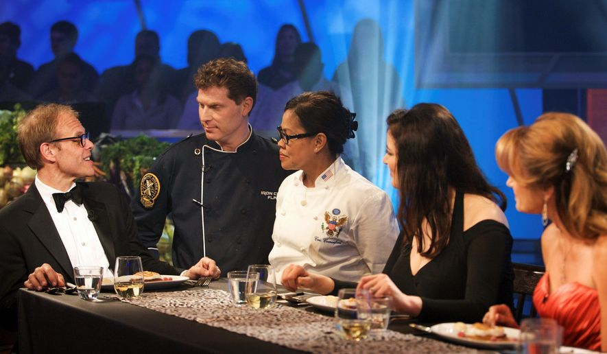 """Food Network via Associated Press Alton Brown (from left) talks with chef teammates Bobby Flay and the White House's executive chef, Cristeta Comerford, at the judging table in Kitchen Stadium in New York. Mrs. Comerford paired with Mr. Flay to win the """"Iron Chef America"""" battle over chefs Emeril Lagasse and Mario Batali."""