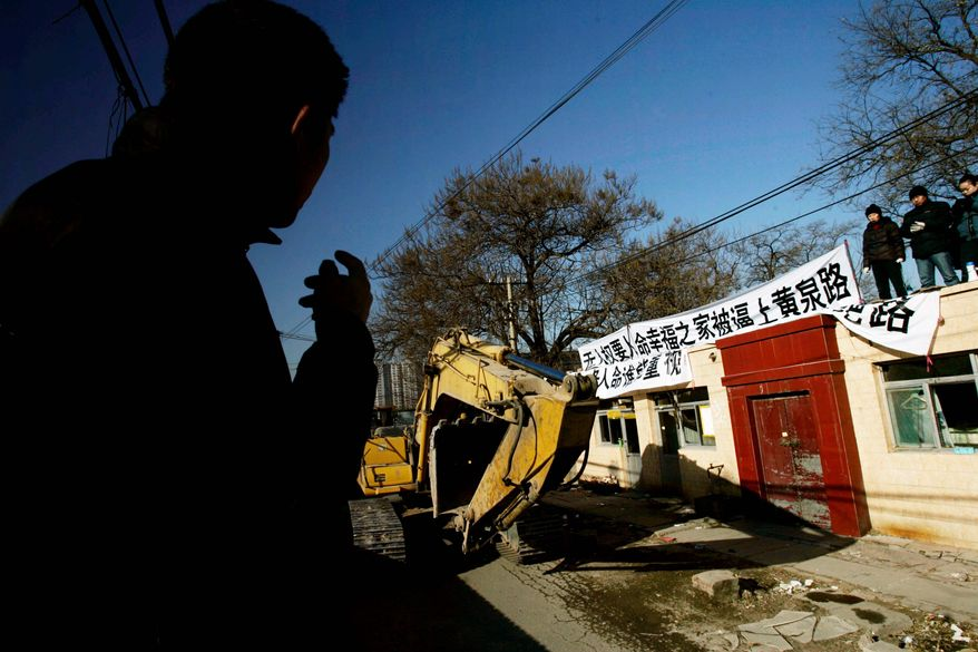 """ASSOCIATED PRESS PHOTOGRAPHS Banners reading """"Forceful demolition. Seven lives, who cares? So much corruption"""" in 2008 mark a home whose owner (left) was among Beijing residents being evicted from their homes in an area to be demolished for real estate developments."""