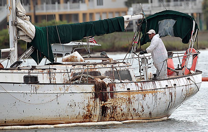 An oily sailboat heads out on a skimming mission in the Perdido Pass in Orange Beach, Ala., Thursday, July 1, 2010. A $4 million oil booming system at the opening of the pass came apart when six foot seas caused by Hurricane Alex battered the coast. (AP Photo/Dave Martin)