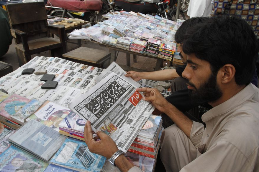 Men read newspapers at a stall in Karachi, Pakistan on Thursday, July 1, 2010. A government-backed proposal to limit Pakistani broadcasters' terror coverage and criticism of the state is stirring outrage among journalists who fear it will stifle the country's feisty, flourishing media. (AP Photo/Shakil Adil)