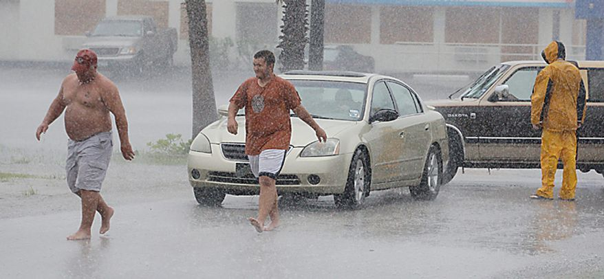 A motorist is assisted by passerbys as the early effects of Hurricane Alex are felt along the Texas coast on  Wednesday, June 30, 2010 in South Padre Island, Texas. (AP Photo/Eric Gay)
