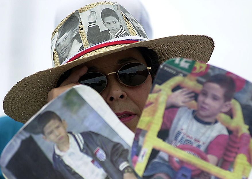 Elian Gonzalez seeks to stay in the US. Silvia Tamajon of Miami stands with other supporters outside the home of Elian Friday afternoon, March 31, 2000. ( Sean Dougherty / The Washington Times )