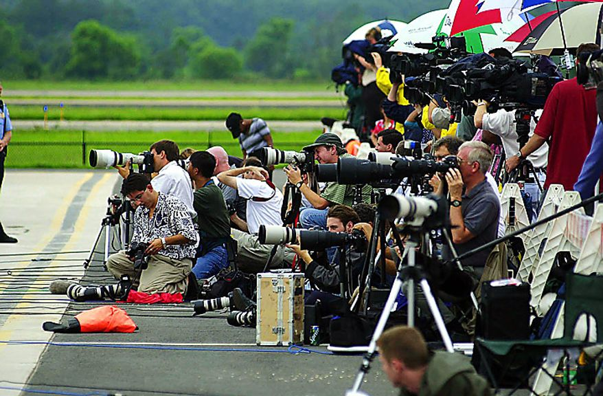 A crowd of media photographs Juan Miguel Gonzalez and his son Elian Gonzalez  as they board a private jet that took them from  Dulles International Airport  to Havana, Cuba, June 28, 2000. ( J.M. Eddins Jr.  / The Washington Times )