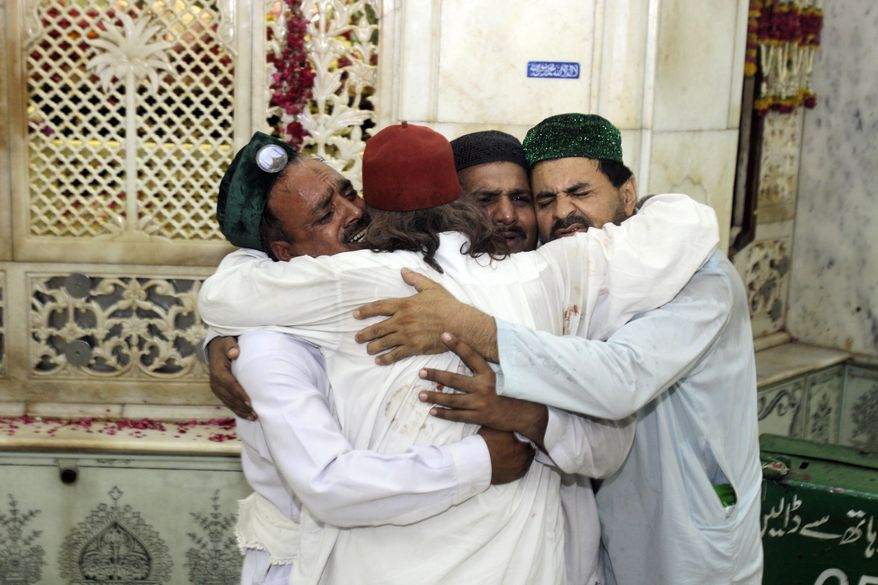 Family members of victims comfort each others after suicide bombers attacked a popular Muslim shrine in the Pakistan city of Lahore late Thursday night, July 1, 2010, killing more than 40 people and wounding 175 others, the city's top official said. (AP Photo/K.M.Chaudary)