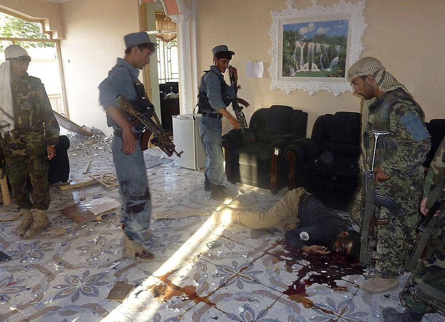 Afghan security forces members stand next to the body of a security guard inside a USAID compound in Kunduz, northern Afghanistan, Friday, July 2, 2010, after it was stormed by militants wearing suicide vests. Six suicide bombers attacked the compound Friday, killing at least four people and wounding several others, officials said. (AP Photo)