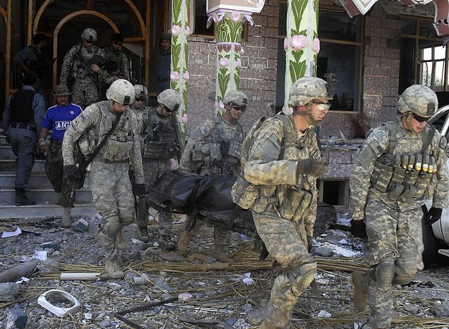U.S. soldiers carry a body at a USAID compound in Kunduz, north of Kabul, Afghanistan, Friday, July 2, 2010, after it was stormed by militants wearing suicide vests. Six suicide bombers attacked the compound Friday in northern Afghanistan, killing at least four people and wounding several others, officials said.  (AP Photo)