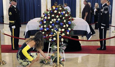 Grace Smiley, 16, of Cross Lanes, W.Va., lays a flower at the casket of Sen. Robert C. Byrd early Friday, July 1, 2010, in Charleston, W.Va. (AP Photo/Jeff Gentner)