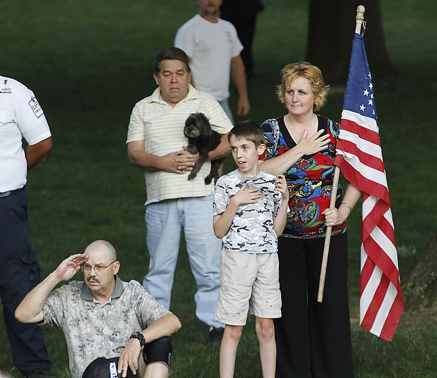 Mourners cover their hearts as the National Anthem is played during an arrival ceremony for the late Sen. Robert C. Byrd, at the Capitol in Charleston, W.Va., Thursday, July 1, 2010. Mr. Byrd will repose at the Capitol until Friday morning when a memorial service will be held.  (AP Photo/Steve Helber)