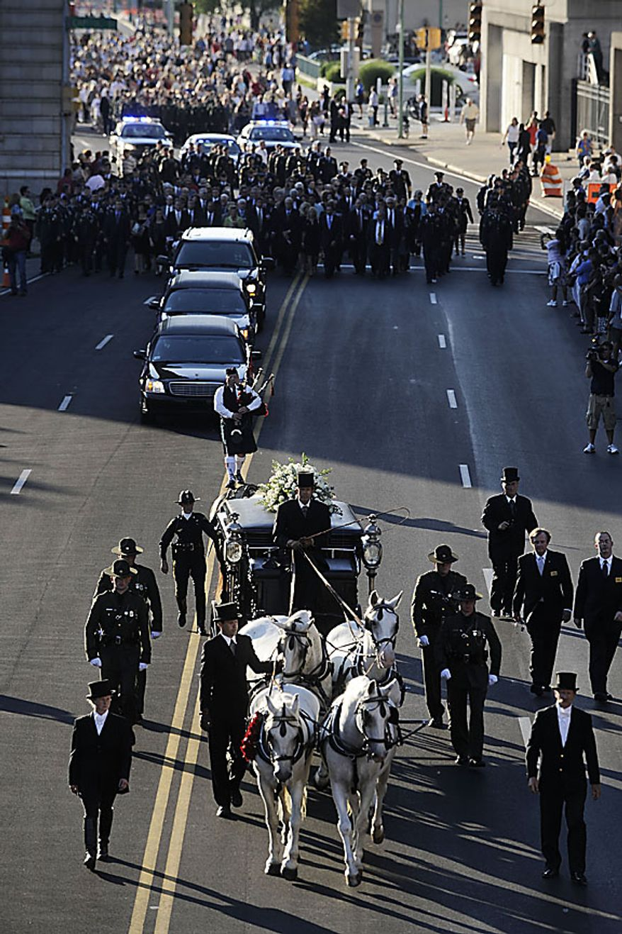 A horse-drawn carriage carrying Sen. Robert C. Byrd leads a funeral procession through the streets of Charleston, W.Va. on Thursday, July 1, 2010. Mr. Byrd will lie in repose at the Capitol until Friday morning when a memorial service will be held.  (AP Photo/Jeff Gentner)