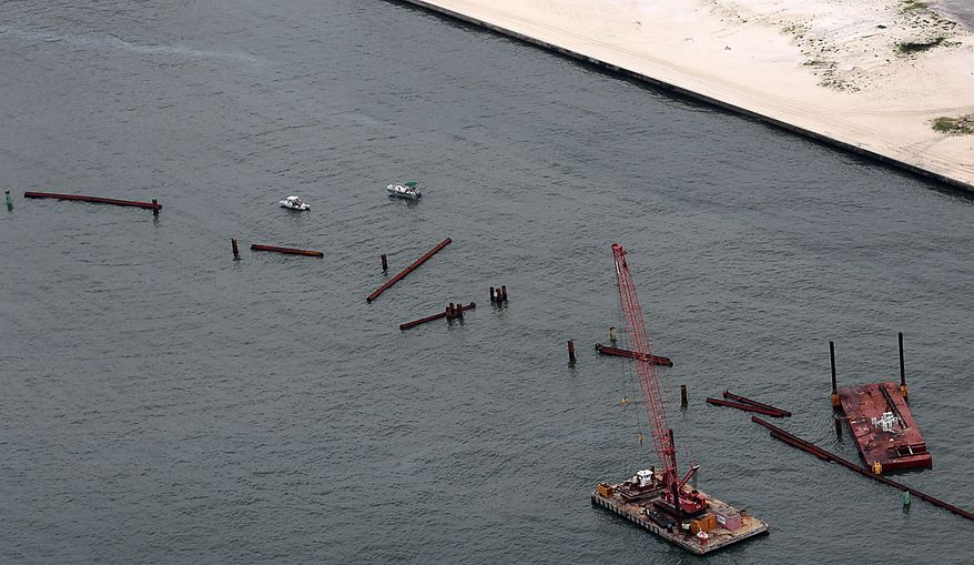Small boats manuver around the $4.6 million broken oil containment boom in the Perdido Pass in Orange Beach, Ala., Friday, July 2, 2010. Heavy seas caused by Hurricane Alex sheared off large bolts on the boom, causing almost 800 feet of the structure to come apart. Oil from the Deepwater Horizon incident is expected to come ashore over the July 4th weekend. (AP Photo/Dave Martin)