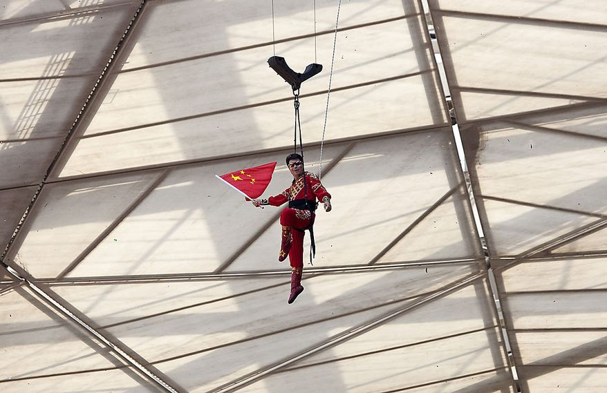 Adili Wuxor waves a Chinese national flag while being lowered to the ground after his two-month tightrope walking performance on top of China's National Stadium, also known as the Bird's Nest, in Beijing Friday, July 2, 2010. Mr. Adili, a Uighur ethnic Dawaz tightrope walking performer, has been walking the tightrope five hours a day on the top of the Bird's Nest over the past 60 days, setting a new Guinness World Record. (AP Photo/Alexander F. Yuan)