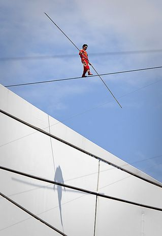 Adili Wuxor walks a tightrope during the last day of his two-month tightrope walking performance on top of China's National Stadium, also known as the Bird's Nest, in Beijing Friday, July 2, 2010. Mr. Adili, an Uighur ethnic Dawaz tightrope walking performer, has been walking the tightrope five hours a day on the top of the Bird's Nest over the past 60 days, setting a new Guinness World Record. (AP Photo/Alexander F. Yuan)