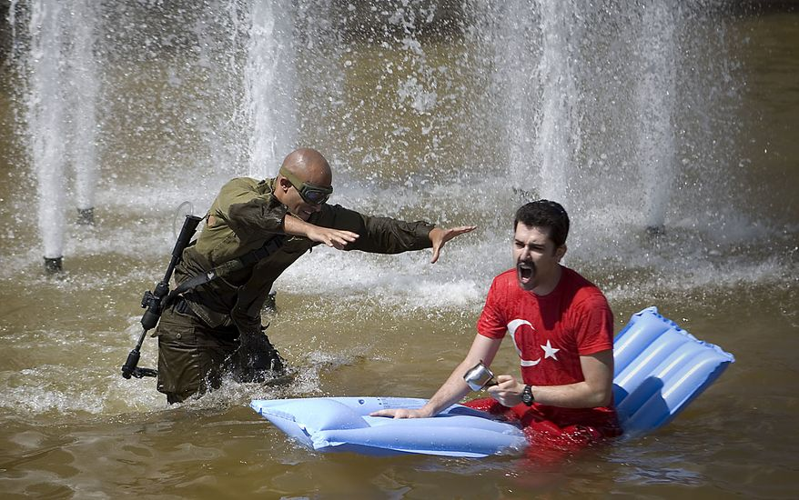 Israelis spray water at each other during a fun water fight event that was staged at Rabin Square in Tel Aviv, Israel, Friday, July 2, 2010. (AP Photo/Ariel Schalit)
