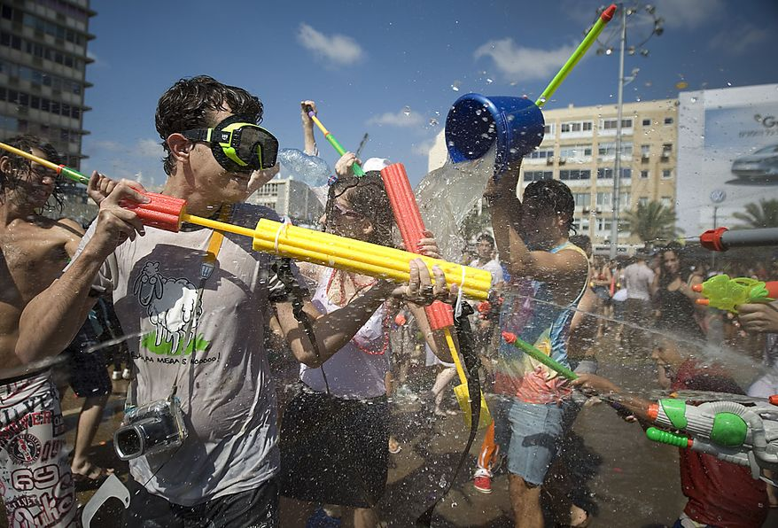 Israelis spray water at each other during a fun water fight event at Rabin Square in Tel Aviv, Israel, Friday, July 2, 2010. (AP Photo/Ariel Schalit)