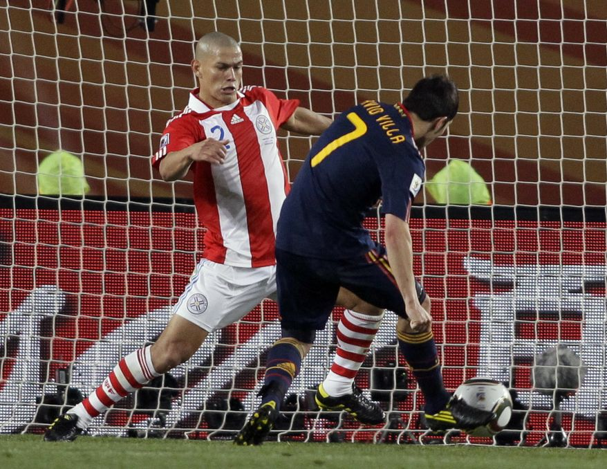 Spain's David Villa, right, scores a goal during the World Cup quarterfinal soccer match between Paraguay and Spain at Ellis Park Stadium in Johannesburg, South Africa, Saturday, July 3, 2010. (AP Photo/Ivan Sekretarev)
