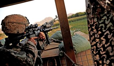 Spec. Donny Mason, a U.S. soldier from Bravo Company, 2nd Battalion of the 508 Parachute Infantry Regiment of the 82nd Airborne, looks through his rifle scope as he stands guard at Combat Outpost Ware in the volatile Arghandab Valley, outside Kandahar City in Afghanistan on Sunday. (Associated Press)