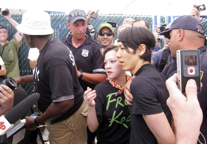 ASSOCIATED PRESS Six-time hot dog eating contest champion Takeru Kobayashi, center, of Japan, is taken into custody by New York police officers after he jumped on stage at the end of the hot dog eating contest in New York's Coney Island on Sunday, July 4, 2010.