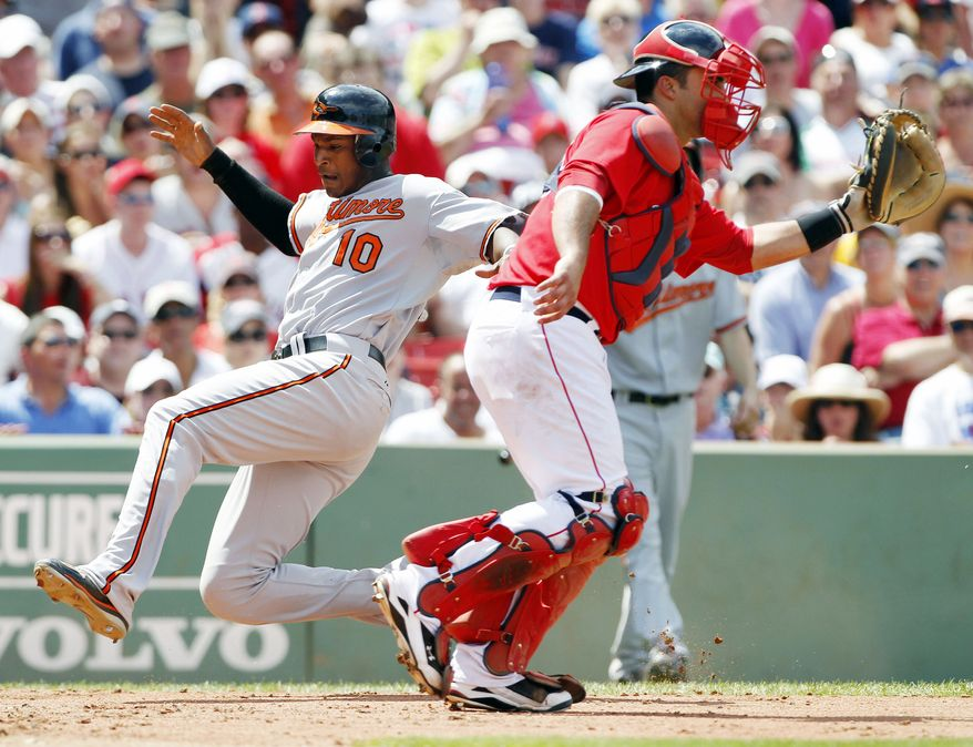 ASSOCIATED PRESS Baltimore Orioles' Adam Jones, left, scores as Boston Red Sox's Gustavo Molina waits for the throw on a single by Orioles' Scott Moore in the fourth inning of a baseball game, Sunday, July 4, 2010, in Boston.