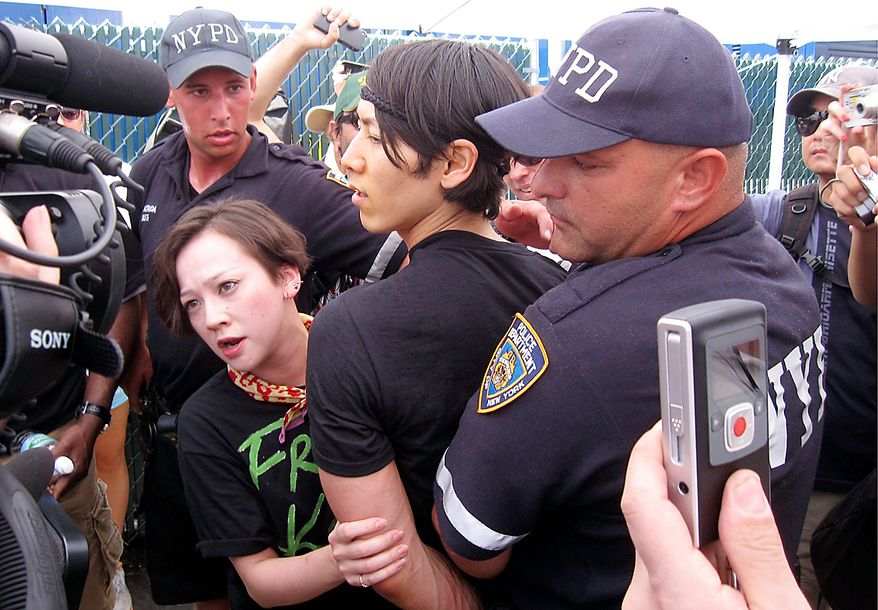 Six-time hot dog eating contest champion Takeru Kobayashi, center, of Japan, is taken into custody by New York police officers after he jumped on stage at the end of the hot dog eating contest in New York's Coney Island on Sunday, July 4, 2010. (AP Photo/Nick Jesdanun)