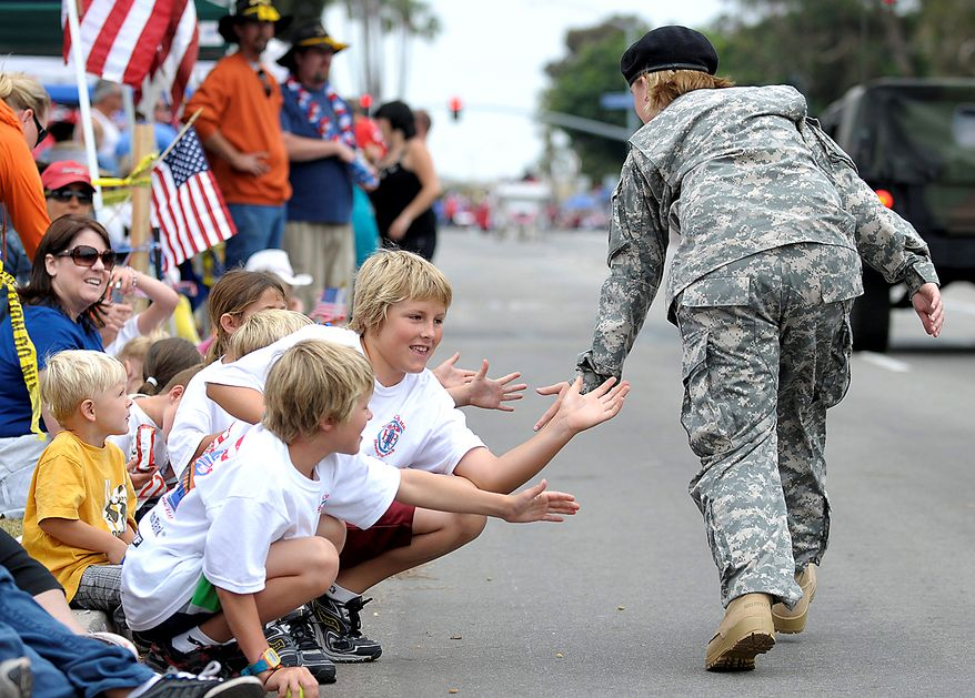 Chase Miller, 10, and Ethan Kemp, 11, center from left, high-five passing veterans at the Huntington Beach Fourth of July Parade on Sunday, July 4, 2010, in Huntington Beach, Calif.  (AP Photo/Adam Lau)