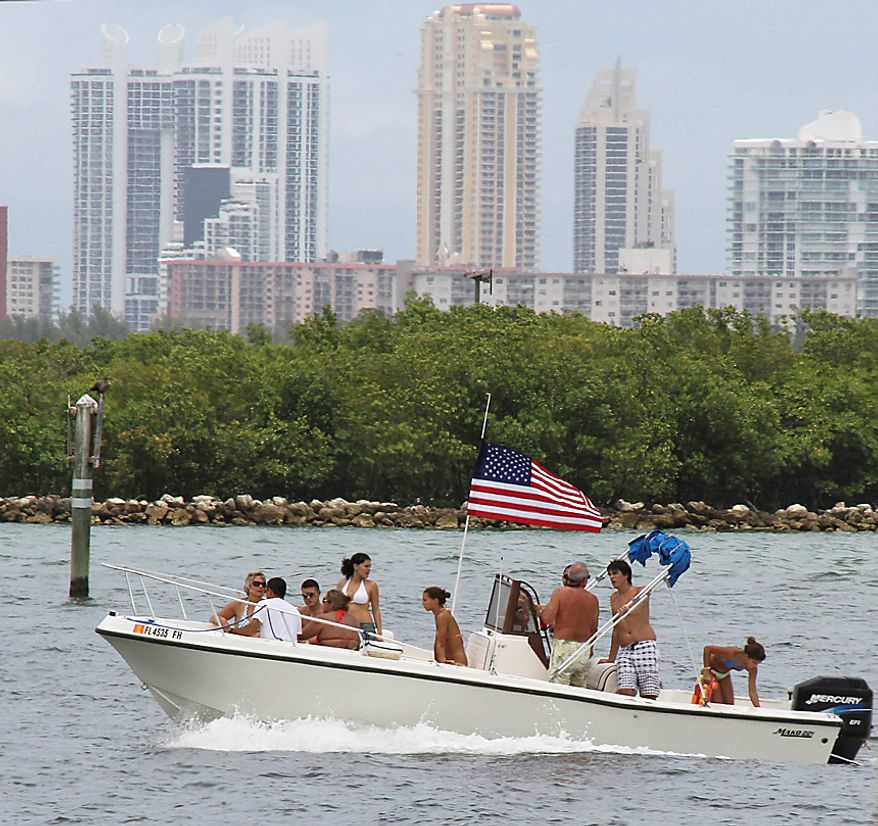Boaters fly an American flag as they motor off Bay Harbor Islands, Fla., Sunday, July 4, 2010. (AP Photo/Wilfredo Lee)