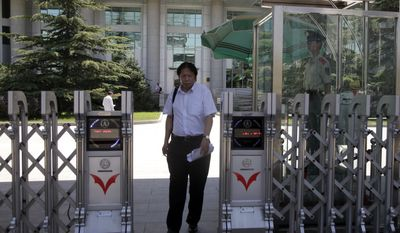 Tong Wei, the lawyer to American geologist Xue Feng, walks out from the Beijing No. 1 Intermediate People's Court where sentencing for Xue Feng was to take place in Beijing, China, Monday, July 5, 2010. Xue Feng, an American geologist detained and tortured by China's state security agents over an oil industry database, was jailed for eight years Monday in a troubling example of China's rough justice system and the way the U.S. government handles cases against its citizens. The court convicted Xue Feng of collecting intelligence for overseas and illegally providing state secrets. (AP Photo/Ng Han Guan)