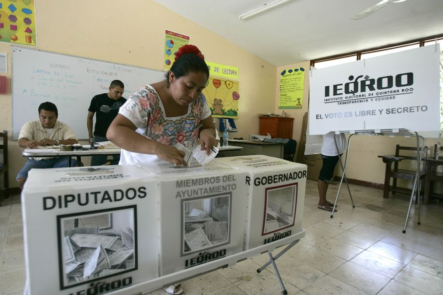 A woman casts her ballot during state elections in the town of Puerto Aventuras in Quintana Roo state, Mexico, Sunday July 4, 2010. A dozen Mexican states held elections Sunday after campaigning besieged by assassinations and scandals that have showcased the drug cartels' power, like in Quintana Roo where one of the main candidates for governor was arrested last month on charges of protecting two cartels. (AP Photo/Israel Leal)