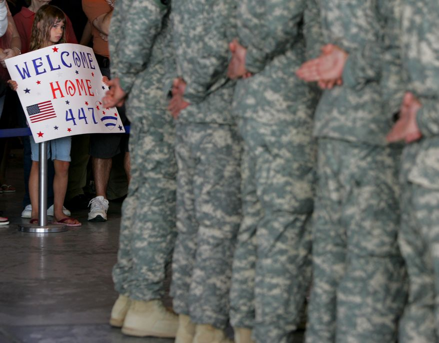 Courtney Cain, 7, of Uniontown, Ohio, holds a sign Friday for her cousin, Seth Koosed, a soldier from the 447th MP Co. returning home from Afghanistan. Koosed and others were honored at a ceremony at the MAPS Air Museum at the Akron-Canton Airport in Green, Ohio. (Associated Press/Akron Beacon Journal, Phil Masturzo)