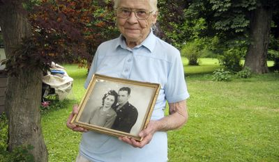In This June 25, 2010 photo, Jean Stevens, 91, holds a photograph from the 1940s of herself and her late husband, James, outside her home in Wyalusing, Pa. Authorities say Stevens stored the bodies of her husband, who died in 1999, and her twin, who died in October 2009, on her property. (AP Photo/Michael Rubinkam)