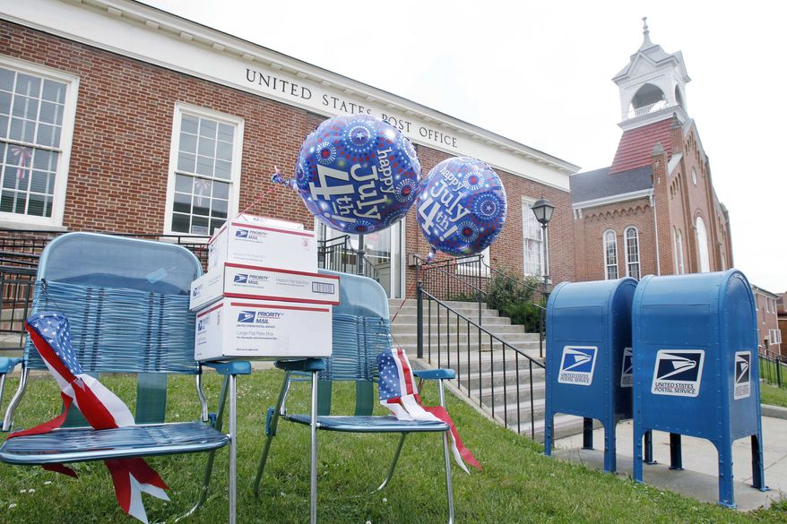 "In this June 29, 2010 photo, a pair of blue chairs decorated with holiday balloons and the postal services ""flat-rate"" boxes are on the lawn in front of the post office in Canonsburg, Pa. Postal officials scheduled a briefing Tuesday, July 6, 2010 to discuss the amount of the increase, which will go to the independent Postal Regulatory Commission for review. (AP Photo/Keith Srakocic)"
