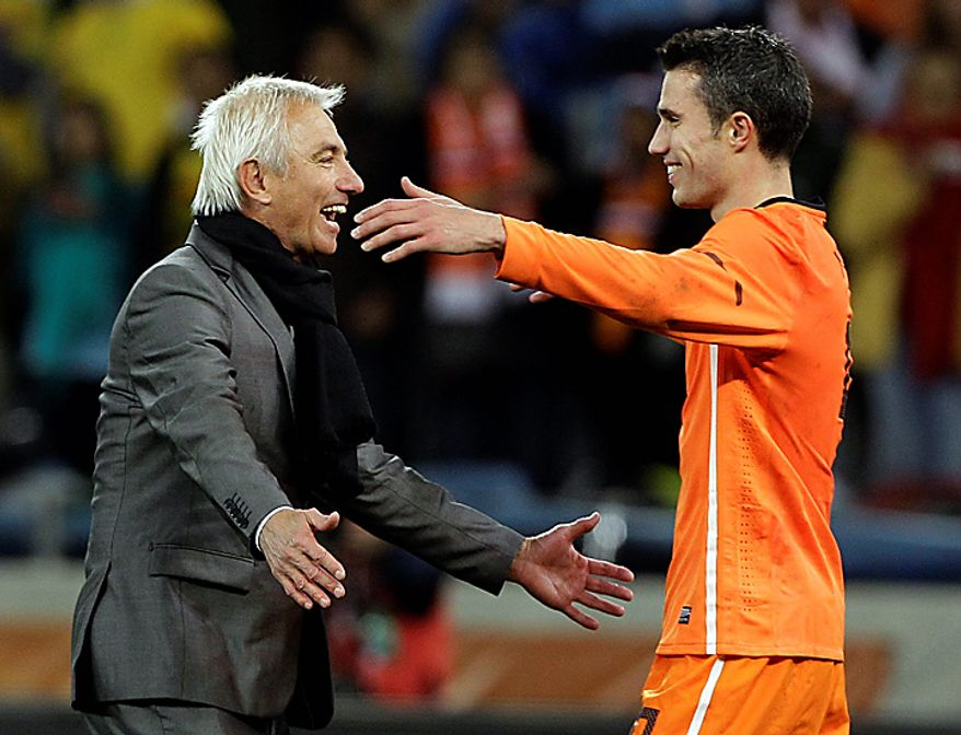 Netherlands' Robin van Persie, right, and head coach Bert van Marwijk  celebrate their 3-2 win after the World Cup semifinal soccer match between Uruguay and the Netherlands at the Green Point stadium in Cape Town, South Africa, Tuesday, July 6, 2010.  (AP Photo/Frank Augstein)
