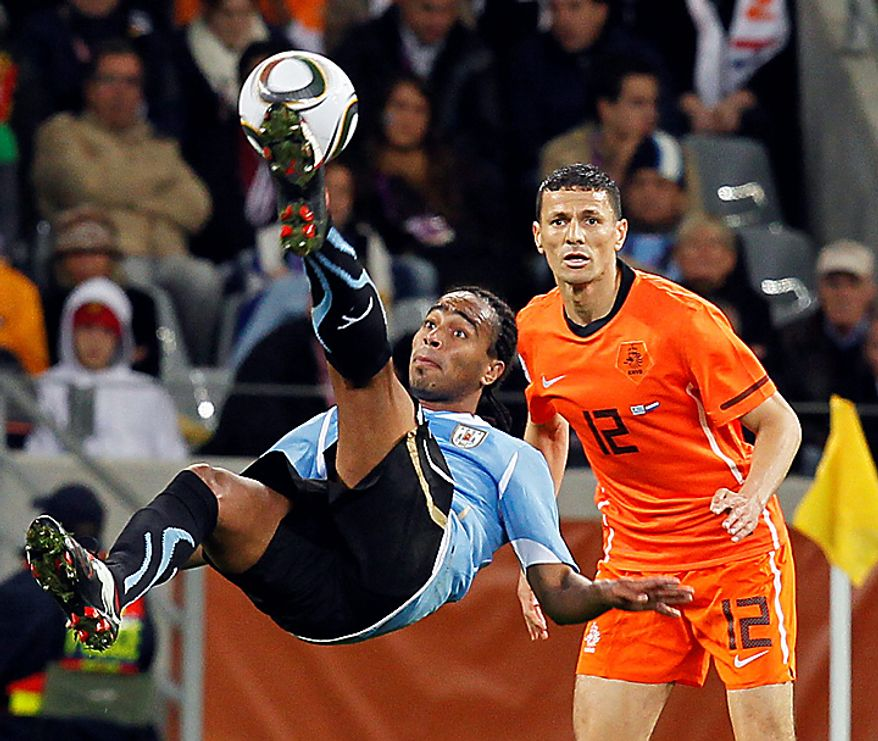 Uruguay's Alvaro Pereira, left, goes for a kick as Netherlands' Khalid Boulahrouz looks on during the World Cup semifinal soccer match between Uruguay and the Netherlands at the Green Point stadium in Cape Town, South Africa, Tuesday, July 6, 2010.  (AP Photo/Eugene Hoshiko)