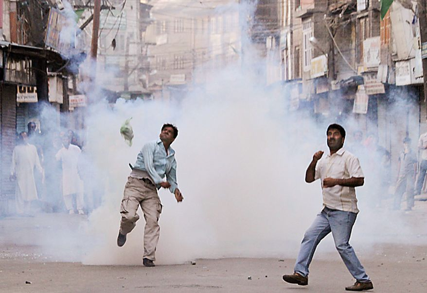 Kashmiri Muslims throws exploded tear gas shells  back at Indian police, after they stopped the funeral procession of Abrar Khan in Srinagar, India, Tuesday, July 6, 2010. Government forces fired on hundreds of rock-throwing protesters in Indian Kashmir on Tuesday, killing three and wounding two others as a seven-day curfew was lifted, locals and officials said. (AP Photo/Mukhtar Khan)