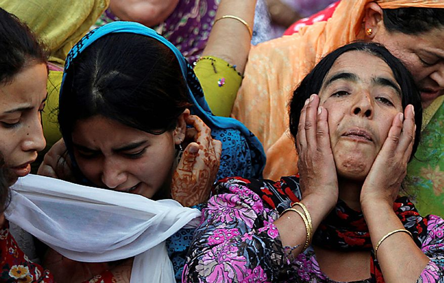 Relatives and neighbors react, near the body of Abrar Khan during his funeral procession in Srinagar, India, Tuesday, July 6, 2010. Government forces fired on hundreds of rock-throwing protesters in Indian Kashmir on Tuesday, killing three and wounding two others as a seven-day curfew was lifted, locals and officials said. (AP Photo/Dar Yasin)