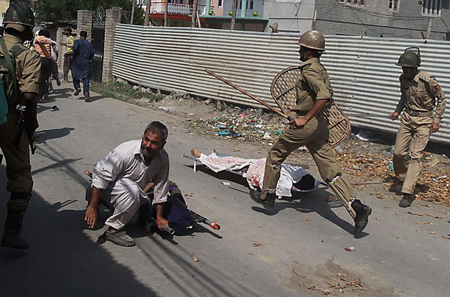 Indian policemen chase Kashmiri mourners as the dead bodies of Muzaffar Bhat and Fayaz Ahamed Wani lie unattended on the ground during their funeral procession on the outskirts of Srinagar, India, Tuesday, July 6, 2010. Government forces fired on hundreds of rock-throwing protesters in Indian Kashmir on Tuesday, killing Wani and wounding two others as a seven-day curfew was lifted, locals and officials said. Bhat was allegedly killed by paramilitary soldiers Monday (AP Photo/Mukhtar Khan)