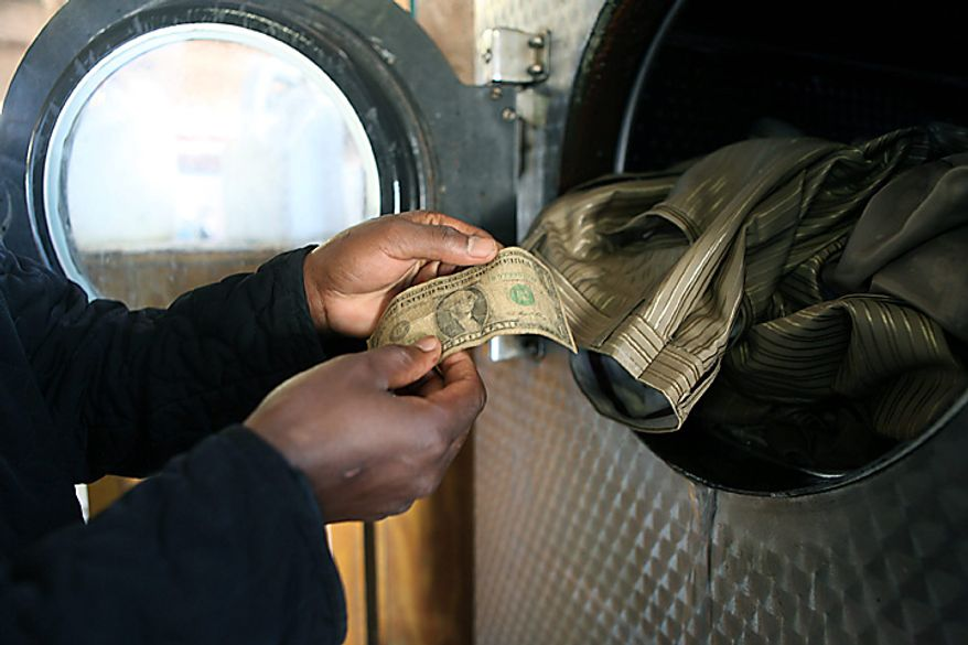 Alex Vaviro places dirty one dollar notes in a washing machine in Harare, Zimbabwe, on Friday, July 2, 2010. The washing machine cycle takes about 45 minutes, and George Washington comes out much cleaner than before in Zimbabwe-style laundering of dirty money. Zimbabweans who have begun trading in the American currency since their own hyper-inflationary notes were abandoned last year say washing their dirtiest cash works. (AP Photo/Tsvangirayi Mukwazhi)