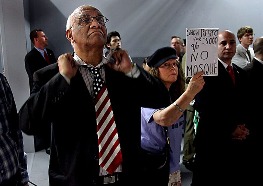 Arish Sahani, left, of New York, puts on an American Flag tie, and Linda Rivera, right, of New York, stand in opposition as groups planning a proposed mosque and cultural center near Ground Zero in Lower Manhattan to be named Cordoba House showed and spoke about their plans for the center at a community board meeting in New York Tuesday, May 25, 2010. Community members both for and against the plan spoke during the meeting.  (AP Photo/Craig Ruttle)