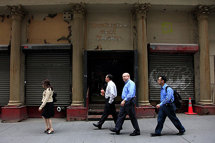People pass a building in lower Manhattan that once housed a Burlington Coat Factory store, Thursday, May 6, 2010, in New York.  A 13-story mosque and Islamic cultural center is planned to replace the building that was damaged by airplane debris on Sept. 11, 2001.  (AP Photo/Mark Lennihan)