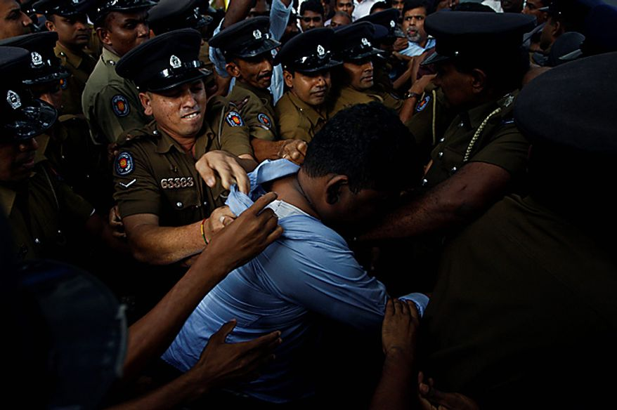Sri Lankan police officials scuffle with a protester outside the UN office during a protest in Colombo, Sri Lanka, Tuesday, July 6, 2010. Police have broken up a blockade of the U.N. office in Sri Lanka's capital and are escorting employees out hours after they were trapped. (AP Photo/Eranga Jayawardena)