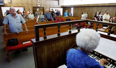 ASSOCIATED PRESS PHOTOGRAPHS Churchgoers sing during a service at Barataria Baptist Church in Lafitte, La. Pastor Eddie Painter in the fishing village told his congregation recently that a silver lining in the otherwise disastrous Gulf of Mexico oil spill might be renewed government commitment to restoring the region's battered coastal marshlands.