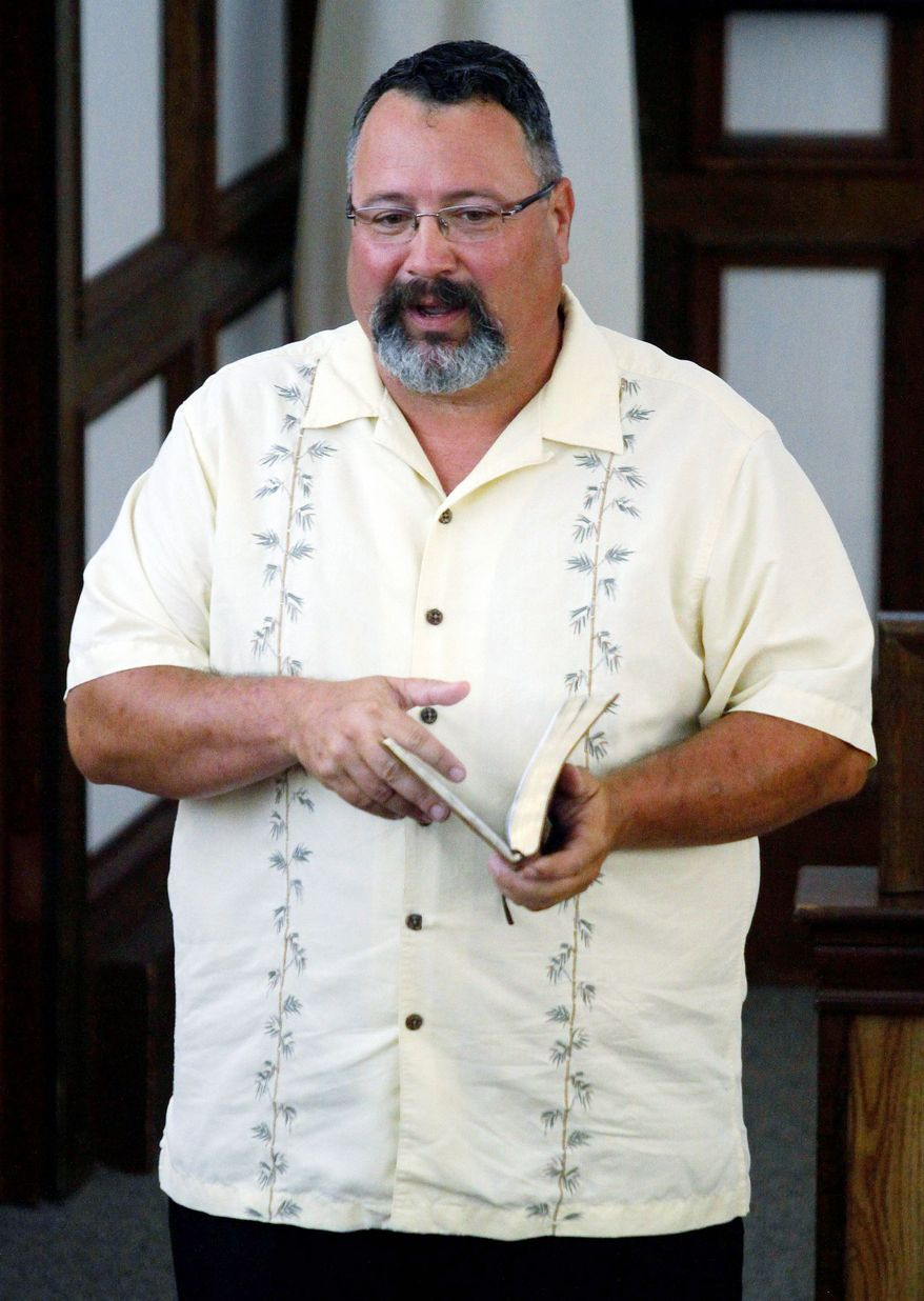 Pastor Eddie Painter, Bible in hand, gives a sermon to churchgoers at Barataria Baptist Church in Lafitte.