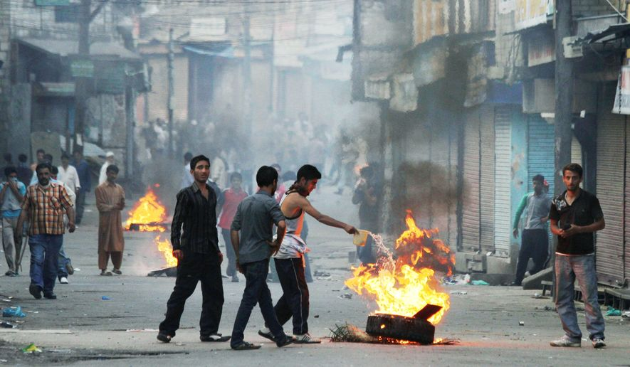 Kashmiri Muslims pour gas on burning tires as they set up roadblocks after Indian police stopped the funeral procession of Abrar Khan in Srinagar, India, on Tuesday. (Associated Press)