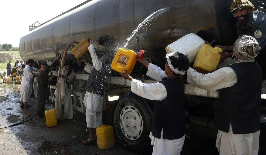 Afghans collect fuel from a tanker shot up in an attack on a NATO supply convoy in Baghlan province, north of Kabul, Afghanistan, Tuesday, July 6, 2010. (AP Photo)