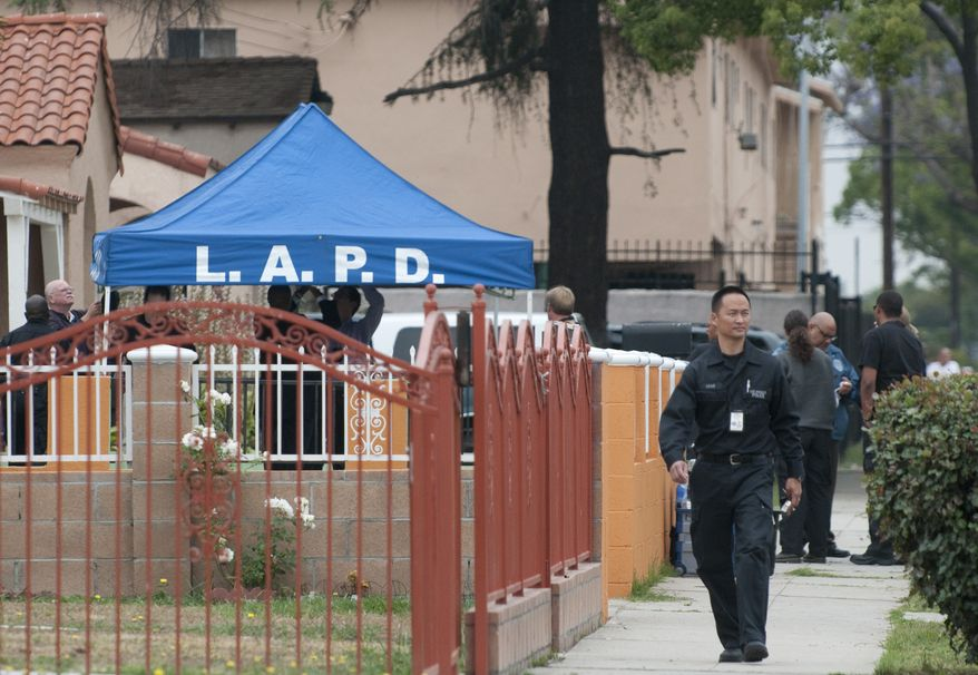 """Los Angeles police setup a tent Wednesday during an investigation of a home on 81st Street in Los Angeles. A law enforcement official said police made an arrest in the so-called """"Grim Sleeper"""" serial killings, in which a man is believed to have killed 11 people since 1985. (Associated Press)"""
