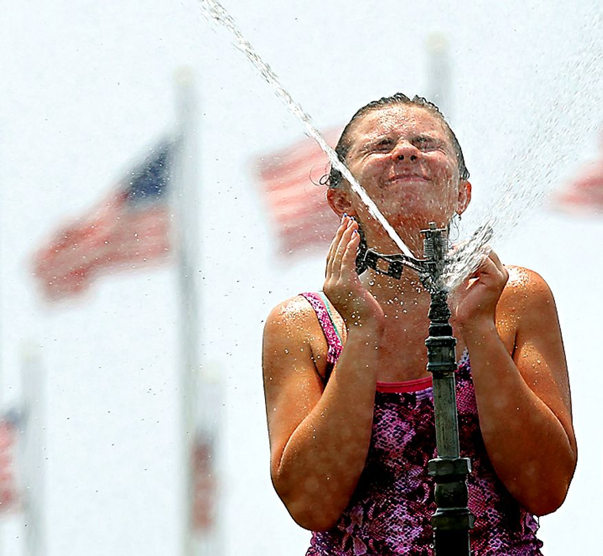 Nicole Pringle, 15, from Glen Burnie, Md., cools off in the spray of a sprinkler on the National Mall in front of the Washington Monument in Washington Wednesday, July 7, 2010. The eastern U.S. cooked for another day as unrelenting heat promised to push thermometers past 100 degrees.(AP Photo/Alex Brandon)