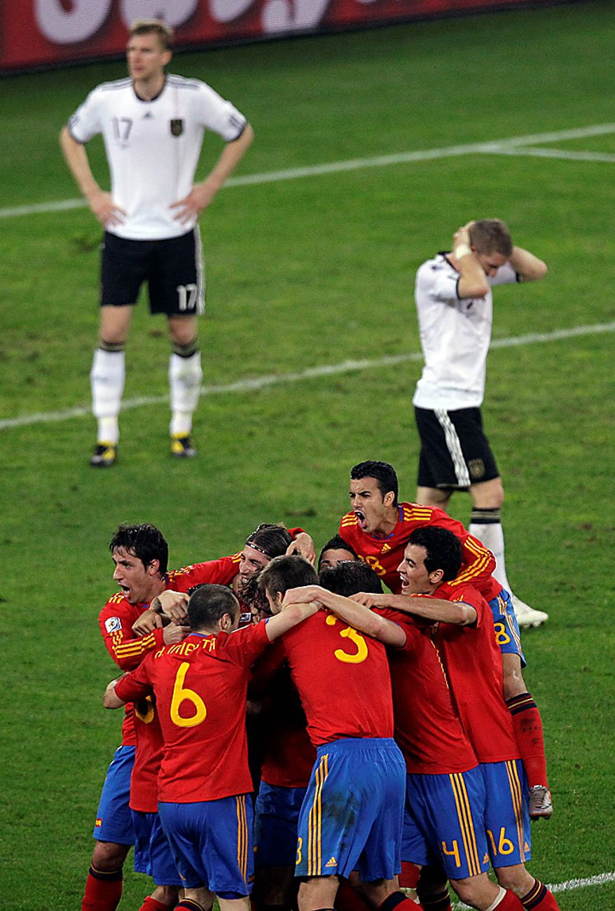 Spain's Carles Puyol is hidden by celebrating teammates after scoring their first goal during the World Cup semifinal soccer match between  Germany and Spain at the stadium in Durban, South Africa, Wednesday, July 7, 2010.  (AP Photo/Hassan Ammar)