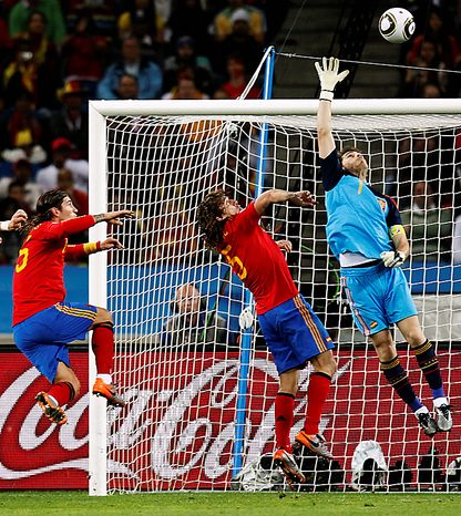 Spain goalkeeper Iker Casillas, right, Spain's Carles Puyol, center, and Spain's Sergio Ramos, left, jump for the ball during the World Cup semifinal soccer match between  Germany and Spain at the stadium in Durban, South Africa, Wednesday, July 7, 2010.  (AP Photo/Luca Bruno)