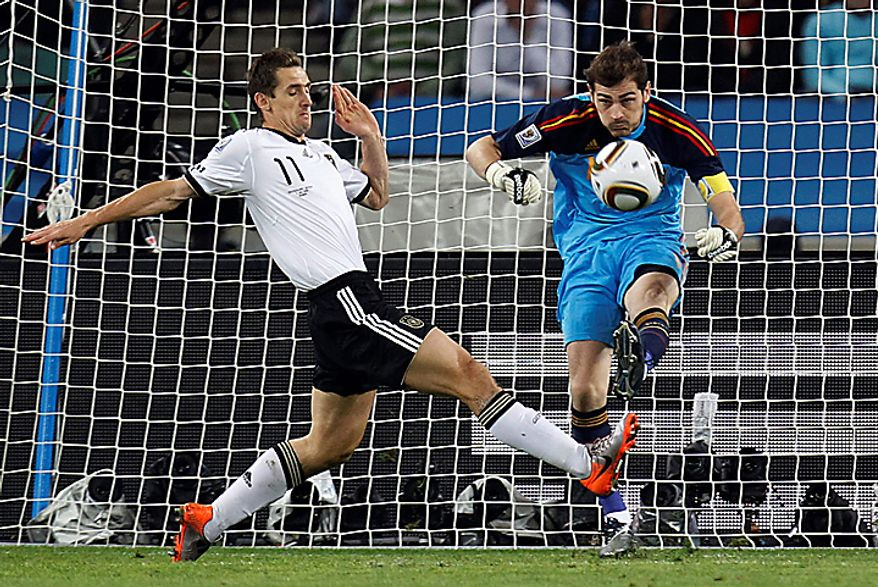Spain goalkeeper Iker Casillas, right, clears the ball past Germany's Miroslav Klose, left, during the World Cup semifinal soccer match between  Germany and Spain at the stadium in Durban, South Africa, Wednesday, July 7, 2010.  (AP Photo/Luca Bruno)